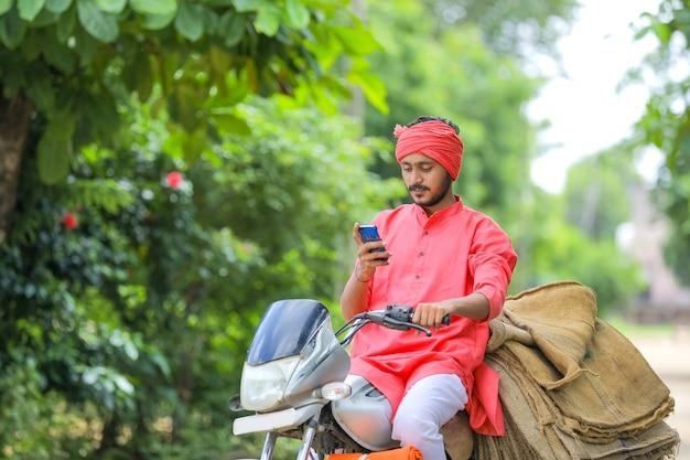 Jonge indiase boer op motor en met behulp van slimme telefoon Premium Foto