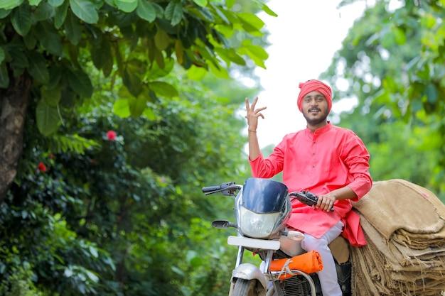 Jonge indiase boer verzamelt jutezak op motor Premium Foto