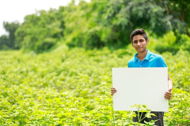 Jonge indiase jongen bedrijf leeg bordje op veld Premium Foto