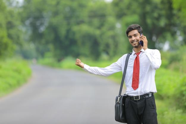 Jonge indiase landbouwingenieur met behulp van slimme telefoon aan de kant van de weg en lift te vragen Premium Foto