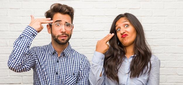 Jonge indiase vrouw en blanke man paar maken van een zelfmoord gebaar, verdrietig en bang vormen een pistool met vingers Premium Foto