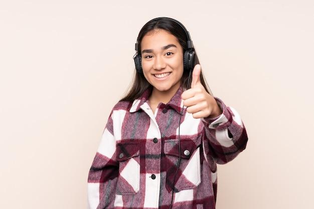 Jonge indiase vrouw geïsoleerd op beige luisteren muziek en met duim omhoog Premium Foto