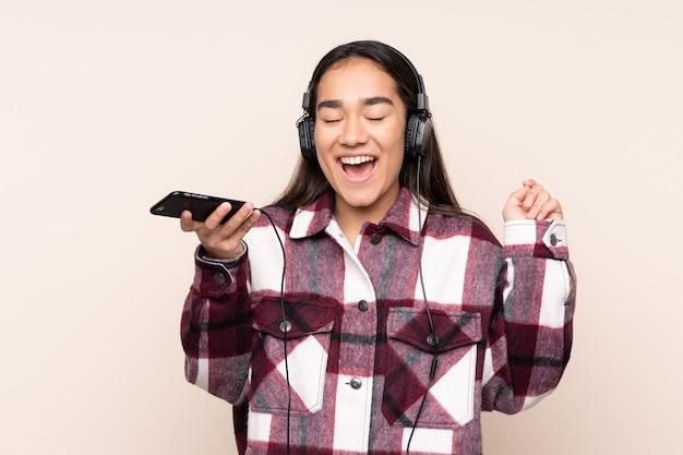 Jonge indiase vrouw geïsoleerd op beige muziek luisteren met een mobiele telefoon en zingen Premium Foto