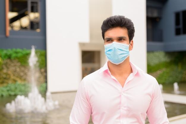 Jonge indiase zakenman met masker denken in de stad buitenshuis Premium Foto