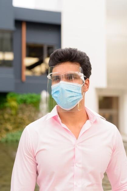 Jonge indiase zakenman met masker en gezichtsschild die in de stad in openlucht denken Premium Foto