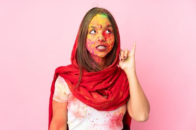 Jonge indische vrouw die met kleurrijk holipoeder op haar gezicht op roze muur aan iets luistert door hand op het oor te zetten Premium Foto