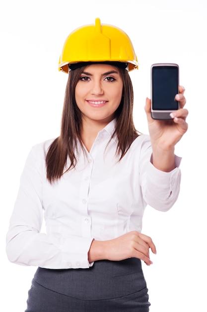 Jonge ingenieur die een slimme telefoon voorstelt Gratis Foto