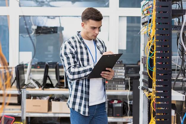 Jonge ingenieur die in serverruimte werkt Gratis Foto