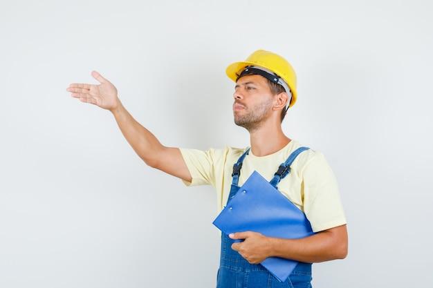 Jonge ingenieur klembord houden en instructies geven in uniform vooraanzicht. Gratis Foto