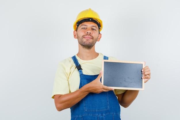 Jonge ingenieur met bord en lachend in uniform, vooraanzicht. Gratis Foto