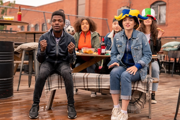 Jonge interculturele paar voetbalfans en hun vrienden zitten op terras, bier met snack hebben en kijken naar wedstrijduitzending Premium Foto