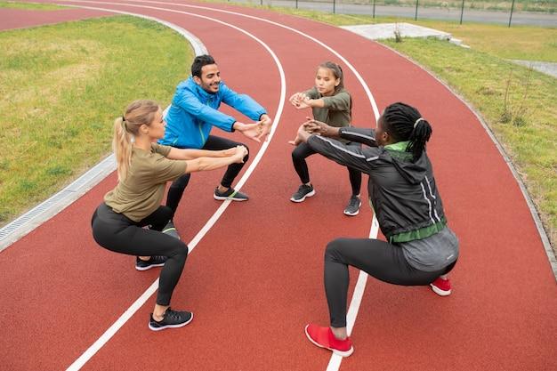 Jonge interculturele vrienden in sportkleding die hun armen naar voren strekken terwijl ze helemaal in het stadion squats Premium Foto
