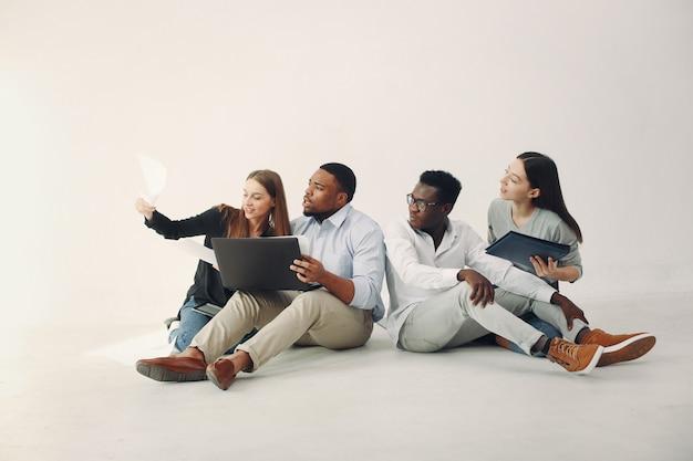 Jonge internationale mensen die samenwerken en de laptop gebruiken Gratis Foto