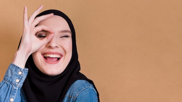 Jonge islamitische blije vrouwelijke holdingsvingers in ok gebaar over haar oog Gratis Foto