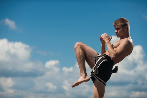Jonge jager schoppen. oefening in de open lucht. knie kick Premium Foto