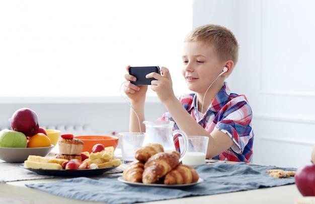 Jonge jongen bij de tafel Gratis Foto
