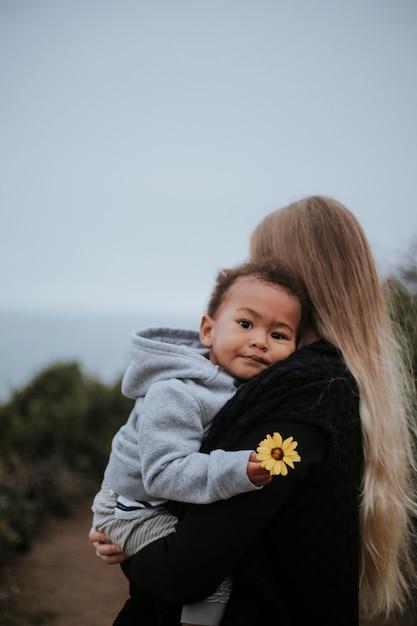 Jonge jongen die een bloem houdt die door zijn mamma wordt gedragen Premium Foto