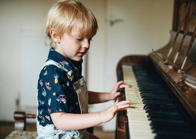 Jonge jongen die een piano speelt Premium Foto