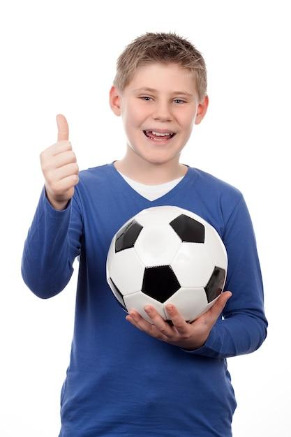 Jonge jongen die een voetbalbal op witte ruimte houdt Gratis Foto