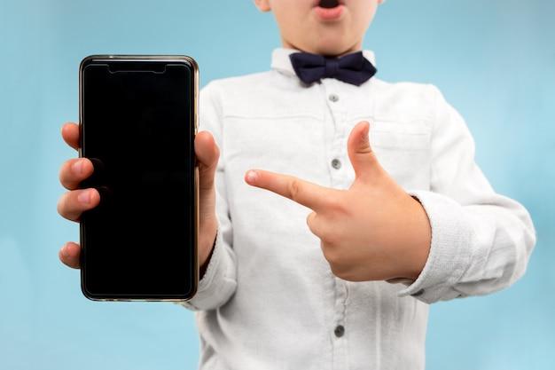 Jonge jongen die lege smartphone houdt Gratis Foto