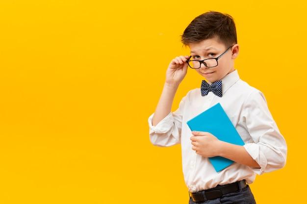 Jonge jongen die met glazen boek houdt Gratis Foto