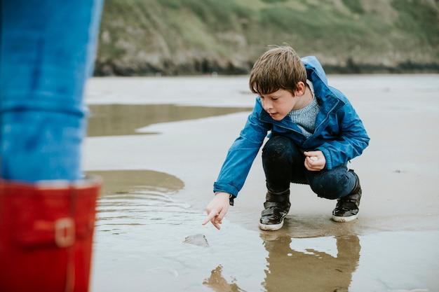 Jonge jongen die op een kwallen op de kust richt Premium Foto