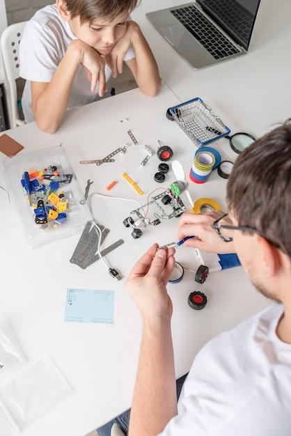 Jonge jongen en leraar plezier samen bouwen van robotauto's in de werkplaats Premium Foto