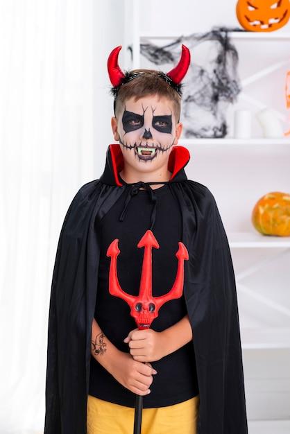Jonge jongen met duivelshoornen die voor halloween stellen Gratis Foto