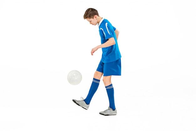 Jonge jongen met voetbal die vliegende schop doet Gratis Foto