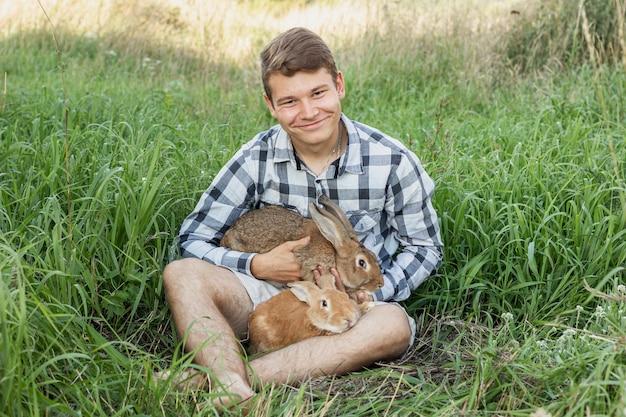 Jonge jongen op boerderij met konijnen Gratis Foto
