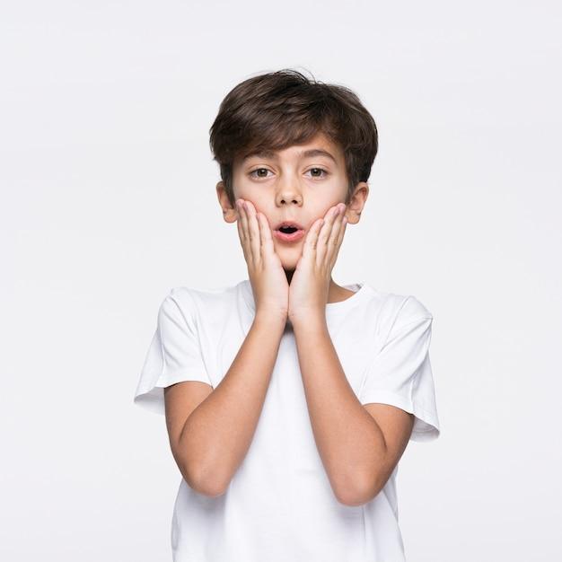 Jonge jongen op witte verraste achtergrond Gratis Foto