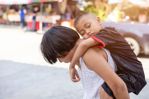 Jonge jongen rideback zijn oude zus en lopen op straat Premium Foto