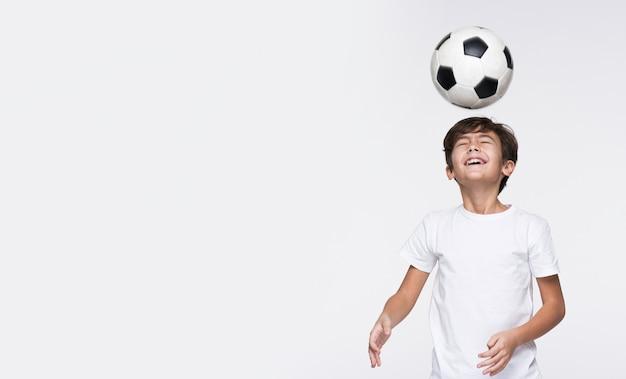 Jonge jongen speelt met voetbal Gratis Foto