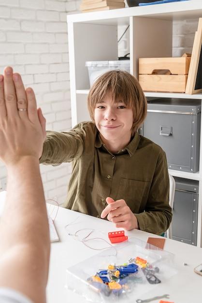 Jonge jongens en leraar hebben plezier bij het bouwen van robotauto's in de werkplaats en geven elkaar een high five Premium Foto