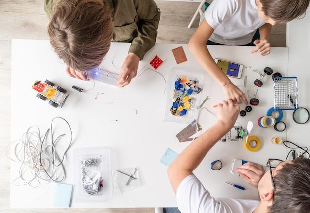 Jonge jongens en leraar plezier maken van robotauto's in de werkplaats, bovenaanzicht Premium Foto