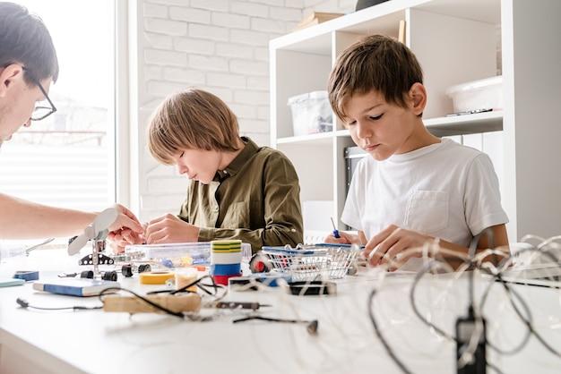 Jonge jongens en leraar plezier samen bouwen van robotauto's in de werkplaats Premium Foto