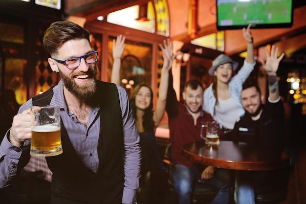 Jonge jongens en meisjes die glazen bier drinken, naar voetbal kijken, lachen en glimlachen Premium Foto
