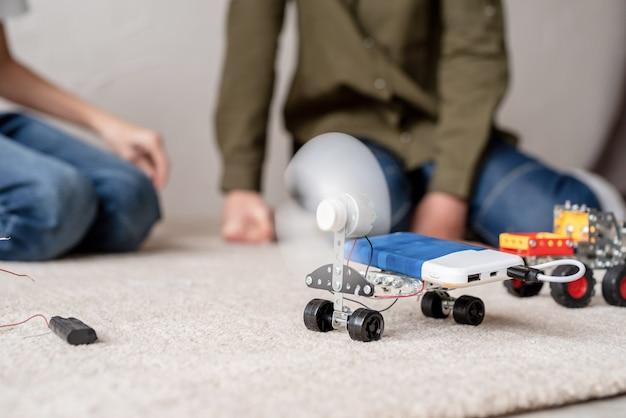 Jonge jongens en plezier hebben bij het samen bouwen van robotauto's in de werkplaats Premium Foto