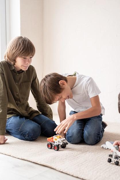 Jonge jongens en plezier hebben bij het samen bouwen van robotauto's op het tapijt Premium Foto