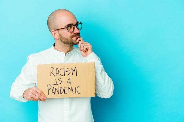 Jonge kale man met een racisme is een pandemie geïsoleerd op een witte muur die zijwaarts kijkt met een twijfelachtige en sceptische uitdrukking Premium Foto