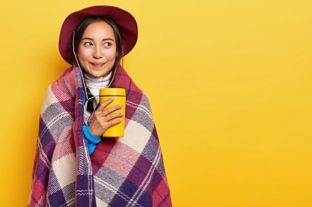 Jonge kalm aangenaam ogende aziatisch meisje staat verpakt in warme plaid, houdt kopje afhaalkoffie, draagt hoed, geniet van tijd voor rust Gratis Foto