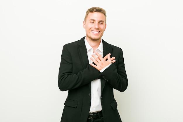 Jonge kaukasische bedrijfsmens die houdend handen op hart lachen, concept geluk. Premium Foto