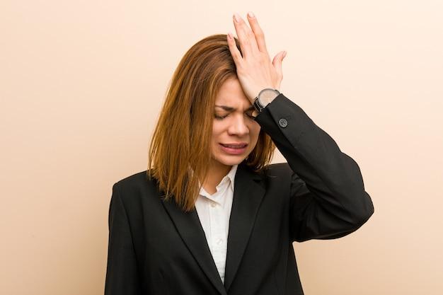 Jonge kaukasische bedrijfsvrouw die iets vergeten, voorhoofd met handpalm slaan en ogen sluiten. Premium Foto