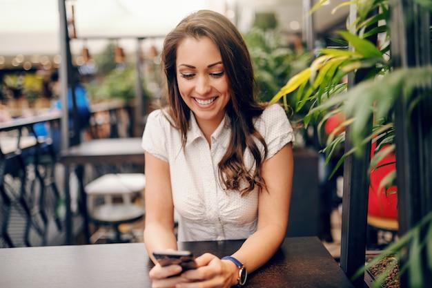 Jonge kaukasische brunette met grote brede glimlachzitting in koffiewinkel en het gebruiken van slimme telefoon voor het lezen van of het schrijven van bericht. Premium Foto