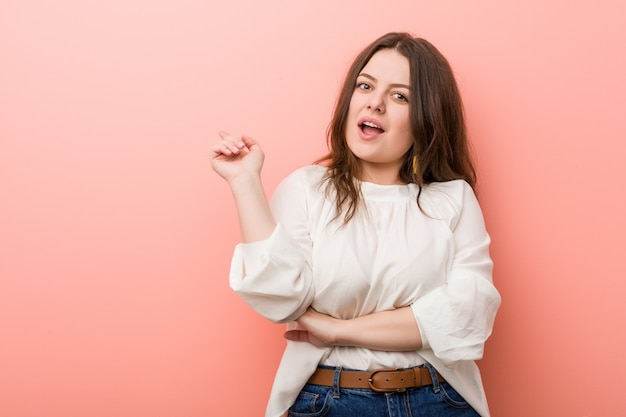 Jonge kaukasische curvy vrouw die zich tegen roze bevindt Premium Foto