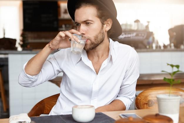 Jonge kaukasische hipster gekleed in wit overhemd drinkwater uit glas tijdens de koffiepauze in de cafetaria. stijlvolle bebaarde man in zwarte hoed ontspannen alleen in moderne café interieur. horizontaal Gratis Foto