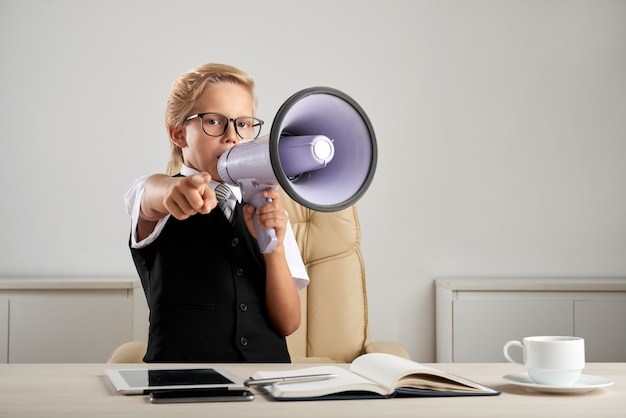 Jonge kaukasische jongen die zich bij uitvoerend bureau in bureau met luidspreker bevindt en vinger richt Gratis Foto