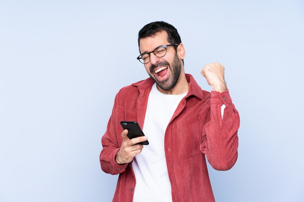 Jonge kaukasische mens die corduroy jasje over blauwe wallwithtelefoon draagt in overwinningspositie Premium Foto
