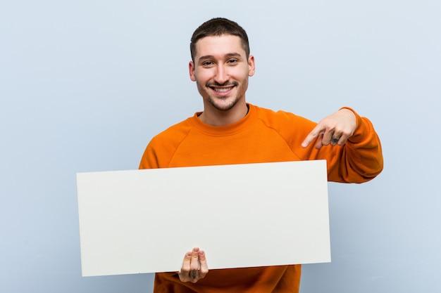 Jonge kaukasische mens die een aanplakbiljet het glimlachen houdt cheerfully wijzend wijs met wijsvinger. Premium Foto