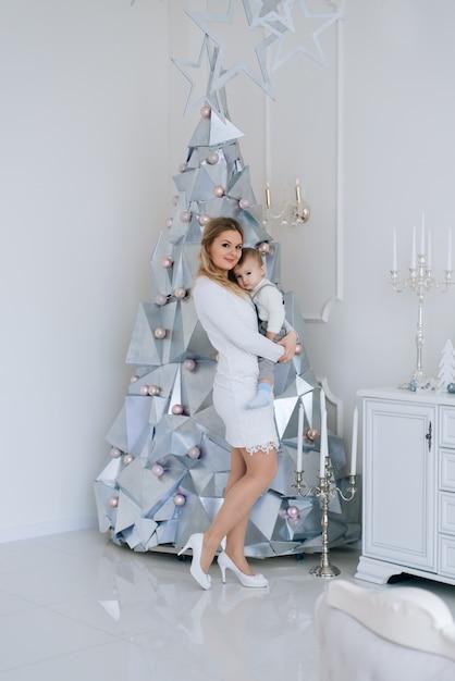 Jonge kaukasische moeder met zoontje in de buurt van de kerstboom. concept van het vieren van wintervakantie en spelen met de baby. Premium Foto